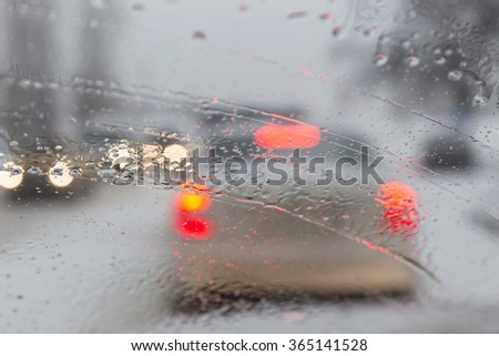 blurry car windshield during a snowfall in the city - stock photo