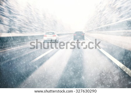 Blurry dangerous car overtaking on highway at heavy snowy conditions. Motion blur visualizies the speed and dynamics. Danger and fast speed driving at the heavy snowy and icy road.  - stock photo