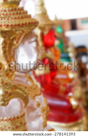 blurry defocused image of clear resin buddha statue wearing asian golden jewelry for background