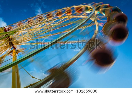 Blurry ferris wheel in motion on blue sky background - stock photo