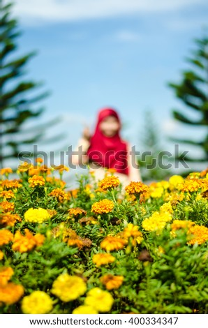Blurry figure of a muslim woman behind orange flower. Shallow DOF. Selective focus on orang flower.