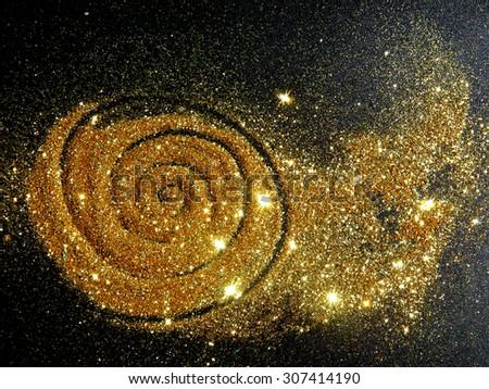 Blurry golden glitter sparkle on black background like a star galaxy - stock photo