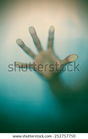 Blurry hand behind matted glass in vintage tone - stock photo