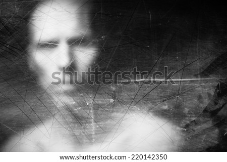 Blurry human face behind dusty scratched glass - stock photo