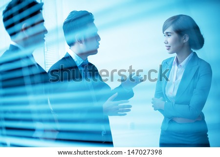 Blurry image of co-workers communicating indoors - stock photo