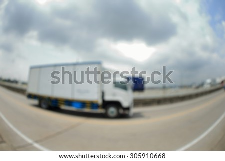 Blurry image of Container truck on free way. Photograph by fisheyes lens.