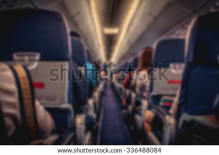 blurry image of interior of airplane with passengers on seats
