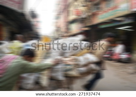 Blurry image of people at street market in India in sunny day, blur background with zooming effect in Chandni Chowk, India - stock photo