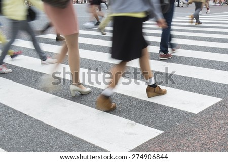 Blurry image of people crossing at crosswalk - stock photo