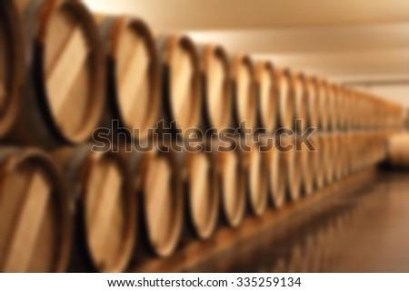 blurry image of wine barrel in cellar - stock photo