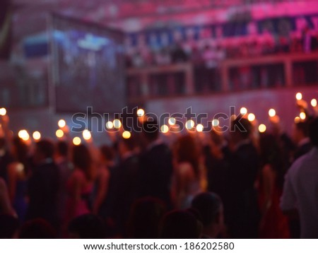 Blurry lights in people hands on prom - stock photo