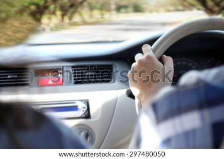 blurry man driving car on the road