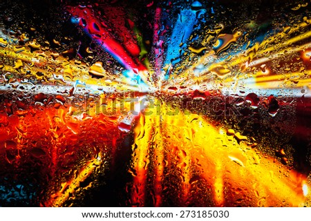 Blurry night city lights in the rain as seen through a wet glass with water droplets  - stock photo