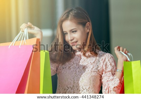 Blurry of happiness, consumerism, sale and people concept - smiling young woman asian with shopping bags - stock photo