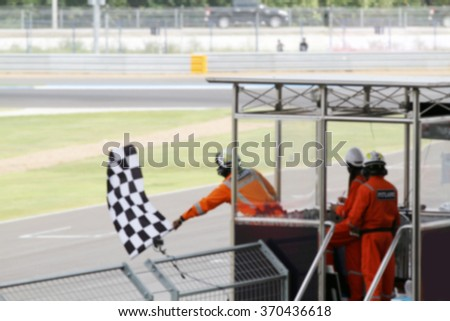 Blurry of Man holding and waving the flag on stand for the race at the finish line and raceway - stock photo
