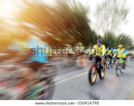 blurry of many people cycling together on road in thailand - stock photo