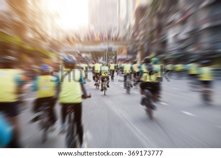 blurry of many people cycling together on road in thailand