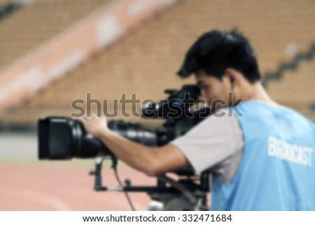 blurry of Professional cameraman and Video camera operator working with his professional equipment - stock photo