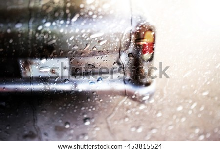 Blurry of Rear view of a vintage car fin,view through the window of rainy day. - stock photo