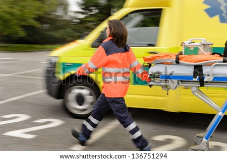 Blurry paramedics in hurry pulling gurney next to ambulance car - stock photo