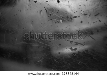 Blurry reflection of a car on old metal grungy surface with rusty scratches and dirty stains. Abstract background. Black and white photo. - stock photo