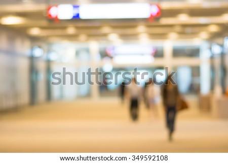 Blurry scene of travelers walking along the terminal - warm tone - stock photo