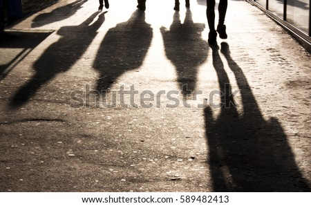 Blurry shadows of people walking towards the camera on the city sidewalk