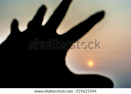 Blurry silhouette hand trying to grab the sun