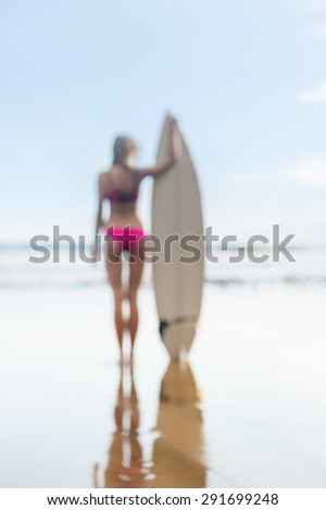 blurry silhouette of a beautiful lady with long hair in a pink swimsuit with surfboard on the sea beach. picture from a dream. image is not in focus. - stock photo