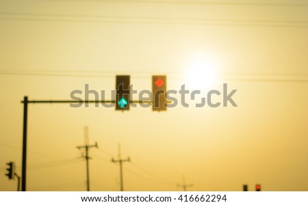 Blurry traffic lights on morning time in the city with warm tone from sunrise - stock photo