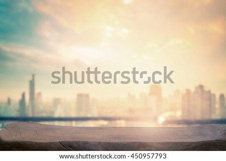 Blurry urban wallpaper concept: Rooftop view of wooden restaurant table and Bangkok city skyline sunset Background.