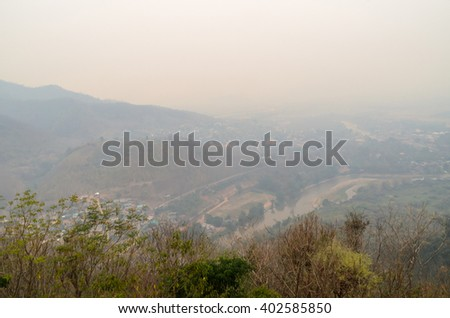 Blurry vision of landscape mountain and city from smog burning forest fires in Thailand - stock photo