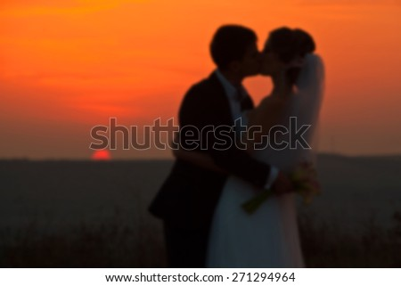 blurry wedding couple in love back light silhouette on sea at the sunset time - stock photo