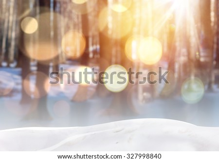 Blurry winter forest with bokeh effect. Christmas background with snow and lights. - stock photo