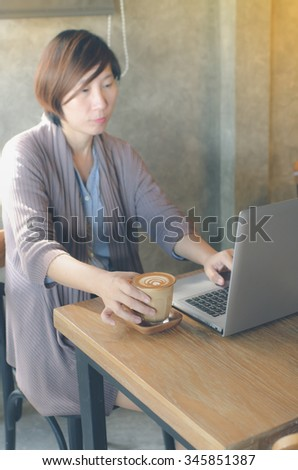 Blury background Asian woman drinking coffee and using computer in cafe, take photo from mirro. Photo filter effect.