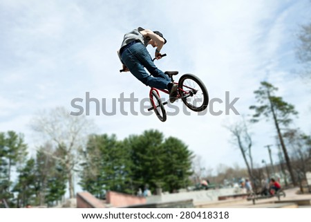 BMX rider athlete spinning his entire bike mid air.  Slight motion blue due to movement. - stock photo