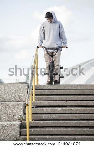 Bmx rider grinding on handrail in urban area, Montreal, Quebec, Canada - stock photo