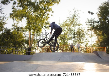 BMX rider training and do tricks in street plaza, bicycle stunt rider in cocncrete skatepark
