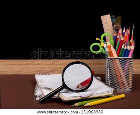 board, books, pencils, opened empty notebook lie on school desk  - stock photo