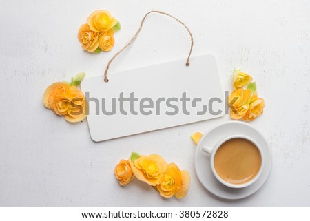 Board for note, flowers and cup of coffee over white wooden background. Top view with copy space, selective focus