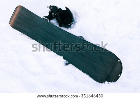 Board for snowboarding and helmet in the snow on snowy background. - stock photo