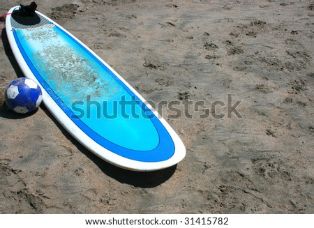 board of surfing on the beach sand with a ball - stock photo