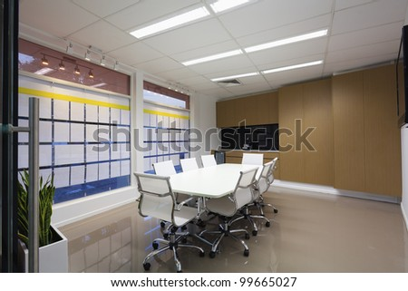 Board room with white chairs and table, new condition.