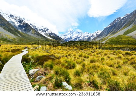 Boarded trail section in Hooker Valley on a track leading to Aoraki, Mount Cook, highest peak of Southern Alps, an icon of New Zealand partially covered in clouds  - stock photo