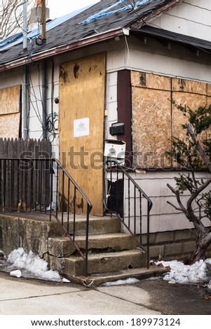 Boarded up condemned home in foreclosure