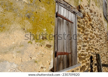 Boarded up old window on a brick and plaster old barn - stock photo
