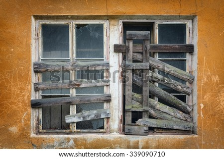 Boarded-up window in an abandoned old building.two old boarded-up window on the wall - stock photo