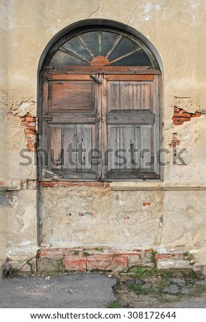 Boarded up wooden window shutter and weathered wall of derelict house. - stock photo