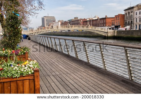 Boardwalk along river Liffey and Ha'penny Bridge in the city of Dublin, Ireland. - stock photo