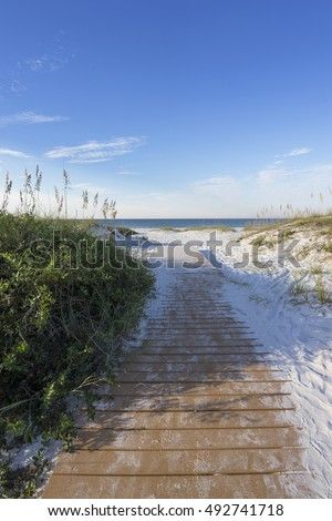 Boardwalk footpath through pristine sand dunes to the Gulf of Mexico in Pensacola Florida, vertical format